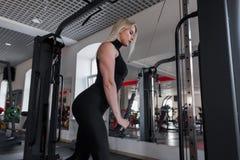Jovem mulher com um corpo bonito em esportes dos jogos do sportswear em um gym Menina no exercício no estúdio da aptidão imagem de stock royalty free