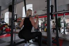 Jovem mulher com um corpo bonito que faz exercícios pesados no gym com um fingerboard do metal Menina na grande forma que faz ocu imagens de stock