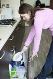Jovem mulher com um escorredor na cozinha Imagens de Stock