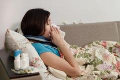 Jovem mulher com um frio Senta-se em uma cama em uma cobertura Foto de Stock Royalty Free