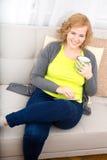 Jovem mulher com um PC da tabuleta no sofá fotos de stock