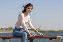 Jovem mulher com um port?til em um banco de parque foto de stock