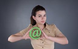 Jovem mulher com @ um símbolo Fotos de Stock