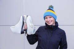 Jovem mulher com um tampão engraçado que guarda os patins brancos imagem de stock royalty free