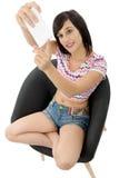 A jovem mulher com um telefone faz um selfie, no branco imagem de stock