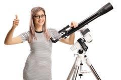 Jovem mulher com um telescópio que dá os polegares acima imagem de stock royalty free