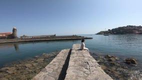 Jovem mulher com um vestido que senta-se na borda do mar Mediterrâneo em Collioure, França filme