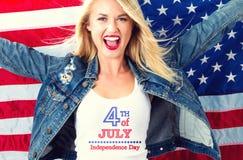 Jovem mulher com uma bandeira americana no quarto de julho Foto de Stock Royalty Free
