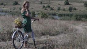 Jovem mulher com uma bicicleta na estrada que fala no telefone vídeos de arquivo