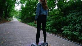 Jovem mulher com uma figura delgada, ondas bonitas que montam um giroscópio no parque Nas calças de brim o bolso é o telefone vídeos de arquivo
