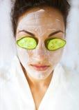 Jovem mulher com uma máscara facial e pepino em sua cara Fotografia de Stock