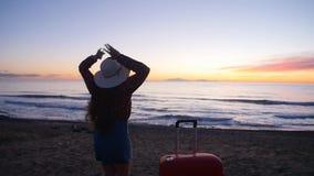 Jovem mulher com uma mala de viagem na praia ensolarada filme