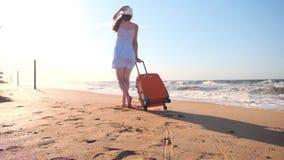 Jovem mulher com uma mala de viagem que senta-se na praia uma moça anda ao longo da praia com uma mala de viagem rodada Cigarros  vídeos de arquivo