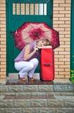 Jovem mulher com uma mala de viagem vermelha Foto de Stock