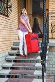 Jovem mulher com uma mala de viagem vermelha Fotos de Stock Royalty Free