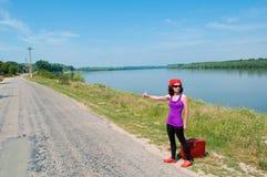 Jovem mulher com uma mala de viagem vermelha que engata um elevador Fotografia de Stock Royalty Free