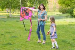 Jovem mulher com uma menina idosa de seis anos pequena que voa um papagaio em um parque verde Foto de Stock Royalty Free