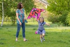 Jovem mulher com uma menina idosa de seis anos pequena que voa um papagaio em um parque verde Imagens de Stock Royalty Free