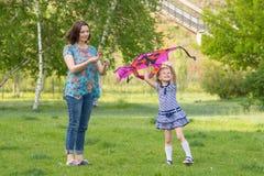Jovem mulher com uma menina idosa de seis anos pequena que voa um papagaio em um parque verde Fotografia de Stock