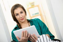 Jovem mulher com uma trança usando o tablet pc fotografia de stock royalty free