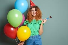 Jovem mulher com ventilador do partido e balões no fundo da cor Celebração do aniversário Foto de Stock Royalty Free