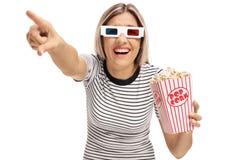 Jovem mulher com vidros 3D e pipoca que aponta e que ri Fotos de Stock Royalty Free