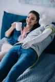jovem mulher com xícara de café que fala ao manequim ao descansar na cama não recompensado imagem de stock royalty free
