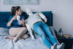 jovem mulher com xícara de café que fala ao manequim ao descansar na cama não recompensado imagens de stock