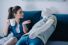 jovem mulher com xícara de café que fala ao manequim ao descansar na cama não recompensado fotografia de stock royalty free