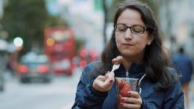 A jovem mulher come morangos frescas nas ruas de Londres filme