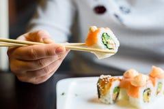 A jovem mulher come rolos de sushi com hashis foto de stock royalty free