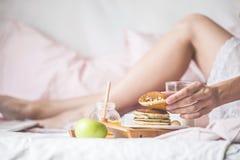 A jovem mulher come um café da manhã saudável na cama imagens de stock royalty free