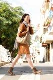 Jovem mulher completa do corpo que fala no telefone celular e na rua de cruzamento Fotografia de Stock