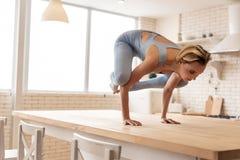 Jovem mulher concentrada que termina extremamente duramente a pose na mesa de cozinha imagens de stock royalty free
