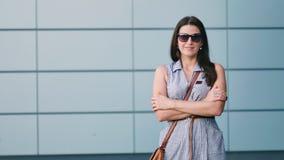 Jovem mulher considerável nos óculos de sol que estão com os braços cruzados video estoque