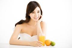 Jovem mulher consideravelmente alegre que guarda o suco de laranjas Fotografia de Stock Royalty Free