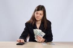 A jovem mulher conta o dinheiro Fotos de Stock Royalty Free