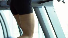 A jovem mulher corre em uma escada rolante no gym, movimento lento filme