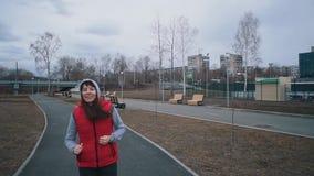 A jovem mulher corre no parque no dia nebuloso filme