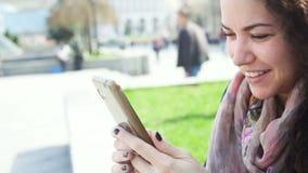 A jovem mulher corrige a composição que olha no telefone do espelho video estoque