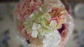 A jovem mulher corrige um arranjo de flor na tabela, flores no vaso de vidro alto, uma decoração festiva da tabela, casamento filme