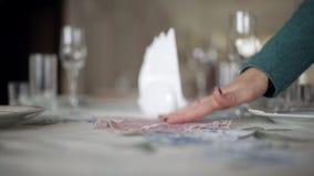 A jovem mulher corrige um arranjo de flor na tabela, flores no vaso de vidro alto, uma decoração festiva da tabela, casamento vídeos de arquivo