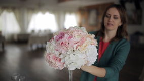A jovem mulher corrige um arranjo de flor na tabela, flores no vaso de vidro alto, uma decoração festiva da tabela, casamento video estoque