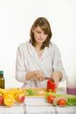A jovem mulher corta o vegetariano da pimenta doce que cozinha a salada Fotografia de Stock