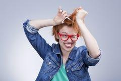 A jovem mulher corta seu cabelo com cabeleireiro das tesouras Foto de Stock