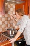 A jovem mulher cozinha o jantar Fotografia de Stock