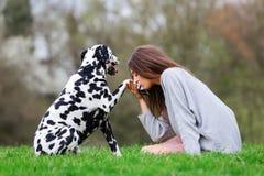 A jovem mulher dá a seu cão Dalmatian um beijo na pata Imagem de Stock