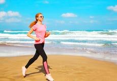 A jovem mulher da aptidão está correndo ao longo da praia Foto de Stock Royalty Free