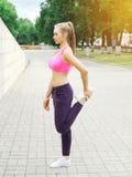 Jovem mulher da aptidão que faz o aquecimento que estica o exercício antes da corrida, atleta fêmea pronto para malhar na cidade  Imagens de Stock Royalty Free