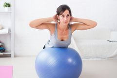 Jovem mulher da aptidão que faz triturações abdominais na bola do ajuste imagem de stock